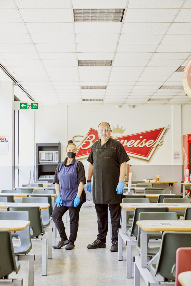 Canteen staff, Bobbie chick and Ted Styles, sanitize tables between lunch sittings at AB-Inbev Magor in Wales, United Kingdom, June 2021. CREDIT: Emli Bendixen for The Wall Street Journal - Budweiser Brewing Group - Emli Bendixen