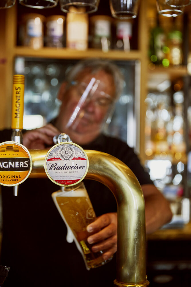 Pub landlord Andrew 'Oz' Cox pulling a pint of Budweiser at The Golden Lion in Magor, Wales where some of AB InBev's products are on offer. CREDIT: Emli Bendixen for The Wall Street Journal - Budweiser Brewing Group - Emli Bendixen